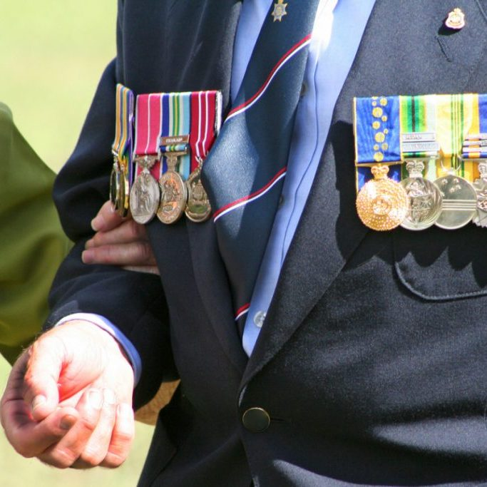 Horizontal close-up of an elderly widow wearing war medals, holding the are of a well-dressed Army veteran whilst laying a floral wreath during an Australian ANZAC Day war memorial at Coomera on the Gold Coast. Both people are wearing medals, including that of the Order of Australia Medal (OAM) and campaign service medals & ribbons including World War 2 (lady - on left) and for Sudan, Bougainville and United Nations peacekeeping operations (man - on right). There is room for copy in the lower right quarter of the image.